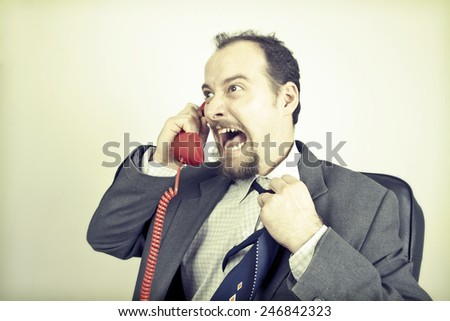 Angry businessman screaming into a red phone - stock photo