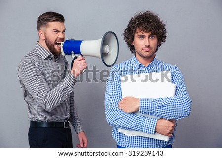 Angry businessman screaming via megaphone to another man over gray background - stock photo