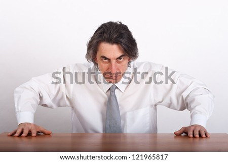 Angry businessman sitting at the table. - stock photo