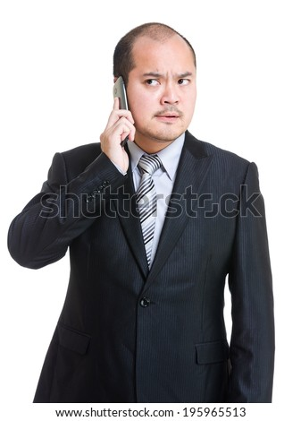 Angry businessman talking on phone - stock photo