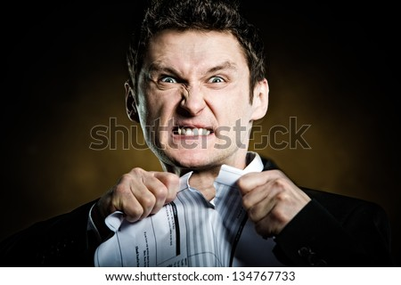 Angry businessman tearing invoice in pieces - stock photo