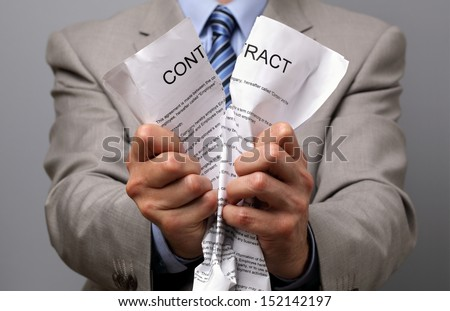 Angry businessman tearing up a document, contract or agreement - stock photo