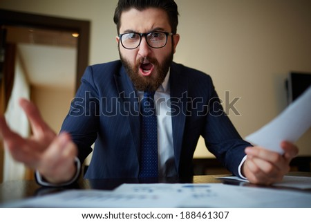 Angry businessman with document shouting at somebody - stock photo