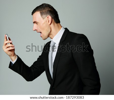 Angry businessman yelling on his cell phone on gray background - stock photo