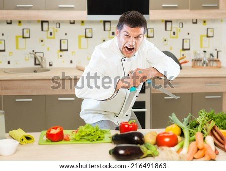 angry chef standing in front of table with vegetables, holding two knifes - stock photo