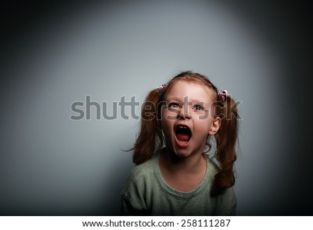 Angry child girl screaming with opened mouth and looking up with evil on dark background - stock photo