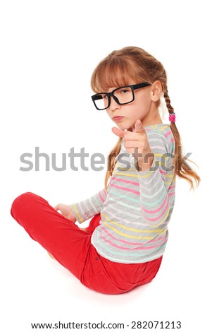 Angry child sitting on floor pointing at camera accusing, isolated on white background - stock photo