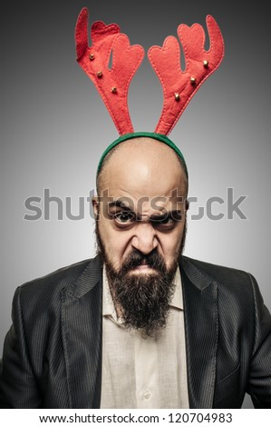 angry christmas bearded man with funny expressions on grey background - stock photo