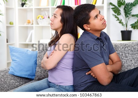 angry couple after  conflict, sitting on couch back to back - stock photo