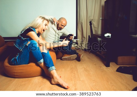 Angry couple playing computer games on tv. concept of leisure entertainment and fun - stock photo