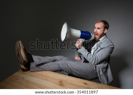 Angry crazy bearded bisnessman sitting with legs on table and shouting in loudspeaker over grey background - stock photo