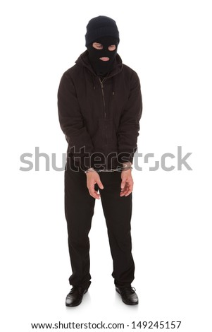 Angry Criminal Locked In Handcuffs Over White Background - stock photo
