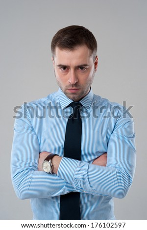 Angry emotion on face of business man isolated on grey background - stock photo