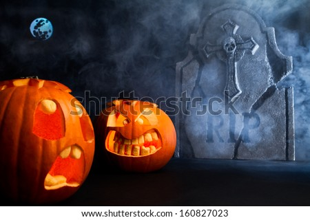 Angry face and scared face of Halloween pumpkins with moon and tombstone on misty dark background. - stock photo