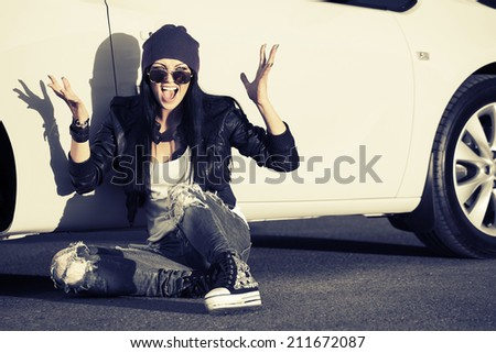 Angry fashion punk woman sitting at the car - stock photo