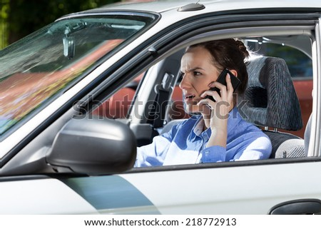 Angry female driver calling on mobile phone, horizontal - stock photo