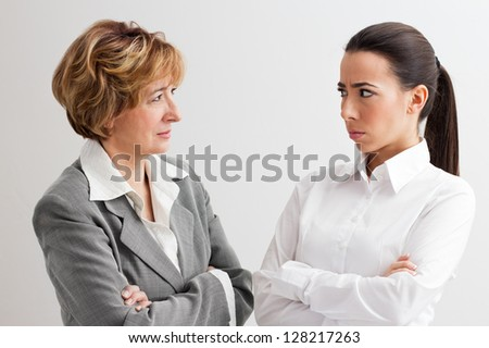 Angry female mature manager standing next to young female worker and staring at her. - stock photo