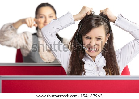 Angry frustrated call center female agent screaming and pulling her hair in rage with female colleague pointing at her from behind. Bad day at work. Stressful work environment. - stock photo