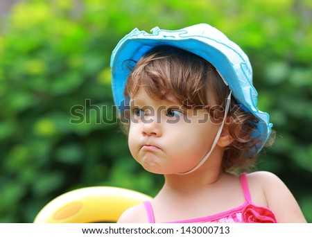 Angry fun girl looking in blue hat on summer green background - stock photo
