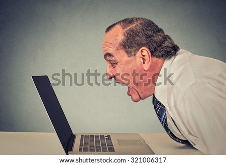 Angry furious business man working on computer, screaming. Negative human emotions, facial expressions, feeling, aggression, anger management issues concept. Side profile man having nervous breakdown  - stock photo