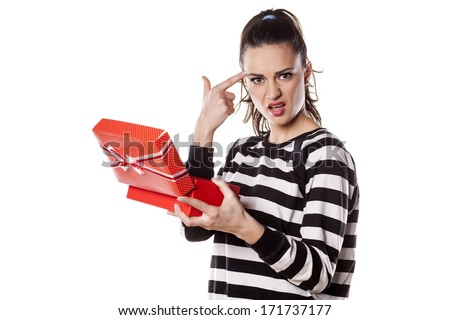 Angry girl holding a gift in her hand and pointing a finger at the head - stock photo