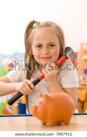 Angry girl ready to break the piggy bank with hammer [focus on the girl] - stock photo