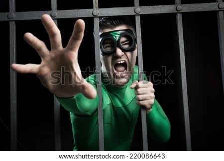 Angry green superhero shouting behind steel prison bars. - stock photo