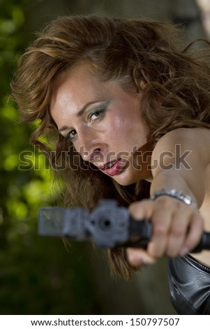 Angry gun woman shooting from a handgun - stock photo
