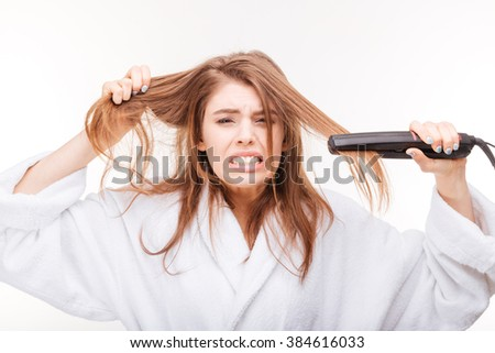Angry irritated young woman straightening her hair using hair straightener over white background - stock photo