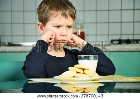 Angry little boy sitting at the dinner table. biscuits on the table and a glass of milk. the boy did not want to eat the food. green and gray kitchen furniture in the background. horizontal - stock photo
