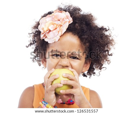 Angry little girl biting an apple, white background - stock photo