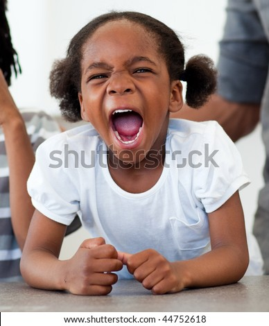 Angry little girl shouting in the kitchen - stock photo