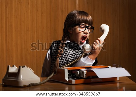 Angry little girl shouting on phone in her office - stock photo