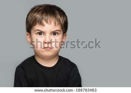 Angry little man head shot posing in front of gray background - stock photo