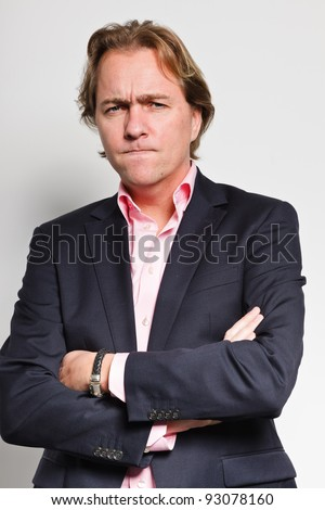 Angry looking young business man blond hair blue suit and pink shirt isolated on white background - stock photo