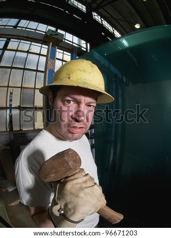 Angry Male Construction Worker with hammer, fisheye - stock photo