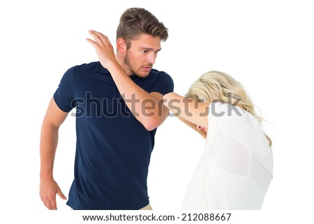 Angry man about to hit his girlfriend on white background - stock photo