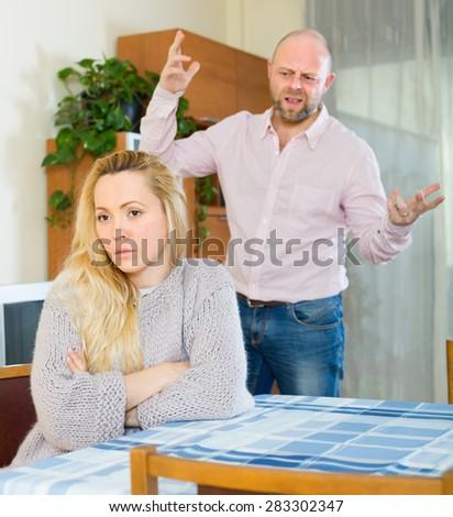 Angry man and young sad woman having quarrel at home - stock photo