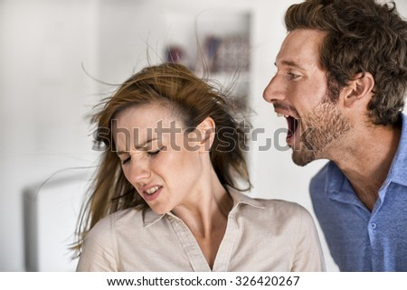 Angry man. He yells at his wife - stock photo
