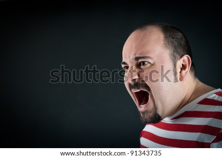 Angry man shouting against black background. - stock photo
