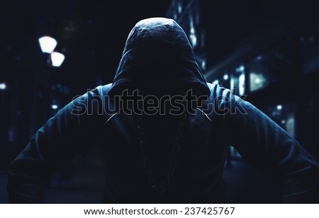 Angry man, sitting with a hood on - stock photo