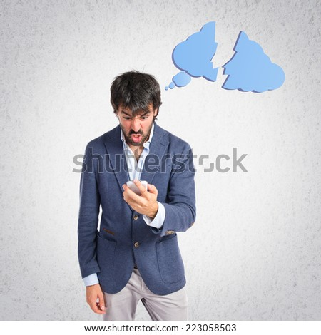 Angry man talking to mobile over grey background - stock photo