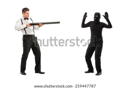 Angry man threatening a burglar with rifle isolated on white background - stock photo