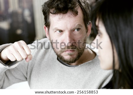 Angry man willing to hit wife in face - stock photo