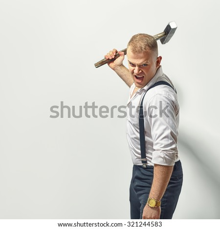 Angry man with hammer - stock photo