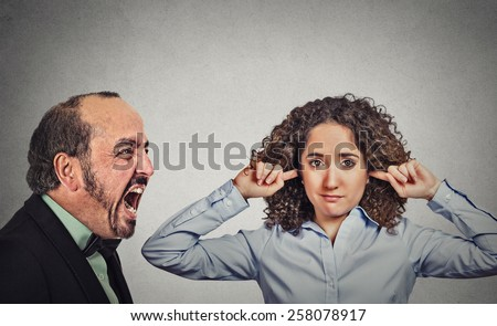 Angry mature man screaming at his young wife who plugs her ears ignoring him isolated on grey wall background. Negative face expression, emotion, confrontation   - stock photo