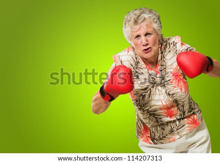 Angry Mature Woman Wearing Boxing Glove Isolated On Green Background - stock photo