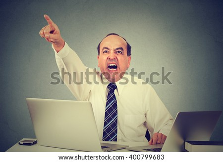 Angry middle aged businessman sitting at his desk and screaming at his employees  - stock photo