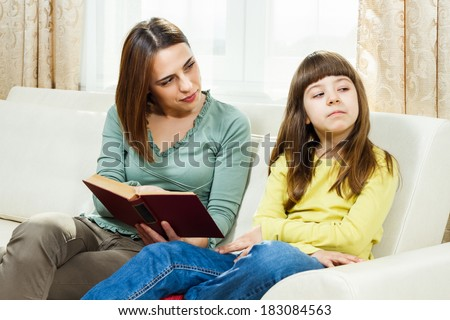Angry mother is showing her daughter a book,she wants that her daughter read more,but little girl doesn't want to,I don`t want to read! - stock photo