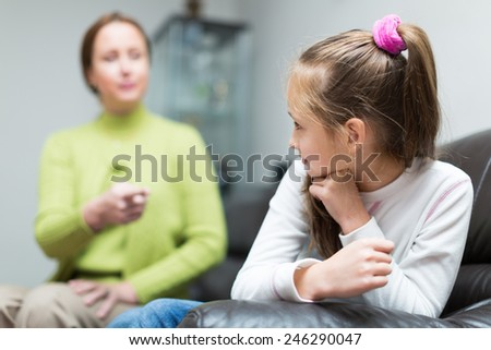 Angry mother scolding little daughter in home interior  - stock photo